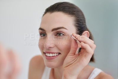 Buy stock photo Shot of a beautiful young woman plucking her eyebrows with a pair of tweezers