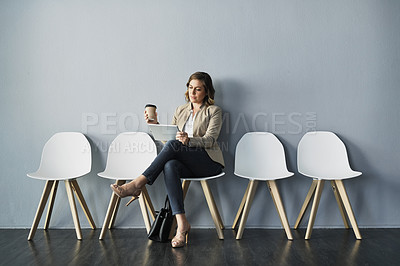 Buy stock photo Full length studio shot of an attractive young businesswoman sitting and holding a coffee cup while using a tablet