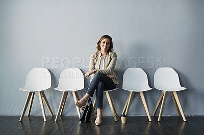 Buy stock photo Portrait of an attractive young businesswoman smiling at the camera against a gray background in the studio