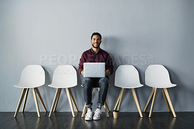 Buy stock photo Portrait of a handsome young businessman using his laptop while sitting against a gray studio background