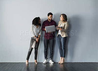 Buy stock photo Full length shot of three young businesspeople talking while holding technology against a gray background in the studio