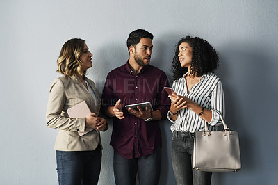 Buy stock photo Cropped shot of three young businesspeople talking while holding technology against a gray background in the studio