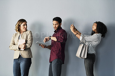 Buy stock photo Cropped shot of three young businesspeople holding technology and standing in a line against a gray background in the studio