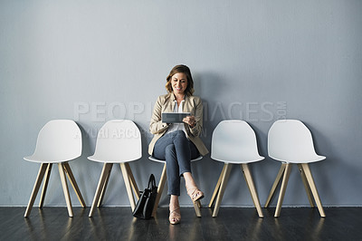 Buy stock photo Full length studio shot of an attractive young businesswoman sitting and using her tablet against a gray background