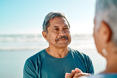 Buy stock photo Cropped shot of an affectionate senior couple holding hands and looking at each other on the beach during the day
