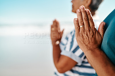 Buy stock photo Cropped shot of an unrecognizable senior couple standing with their palms together in meditation on the beach during the day