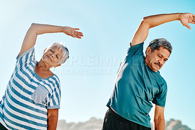 Buy stock photo Cropped shot of a focused senior couple stretching together on the beach during the day