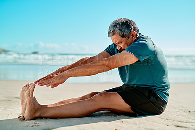 Buy stock photo Full length shot of a handsome senior man sitting and stretching his legs on the beach during the day
