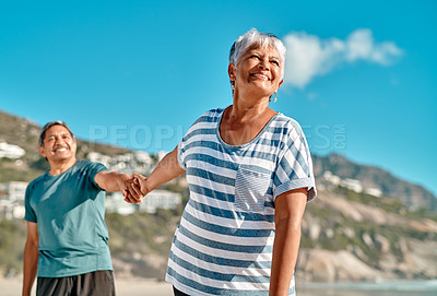 Buy stock photo Cropped shot of a playful senior couple holding hands on the beach during the day