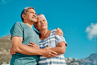 Buy stock photo Cropped shot of an affectionate senior couple standing hugging each other on the beach during the day