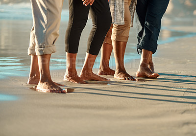 Buy stock photo Cropped shot of an unrecognizable group of people standing next to each other on the beach during the day