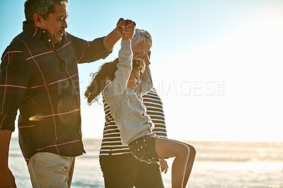 Buy stock photo Cropped shot of a happy senior couple playing with their granddaughter on the beach during the day