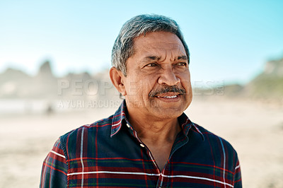 Buy stock photo Headshot of a handsome senior man looking into the distance while on the beach during the day