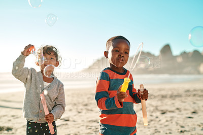 Buy stock photo Cropped shot of two young children playing and blowing bubbles on the beach during the day