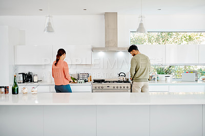 Buy stock photo Rearview shot of a young couple preparing a meal in their kitchen