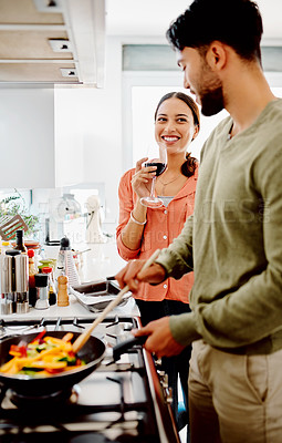 Buy stock photo Shot of a man cooking at home while his wife keeps him company