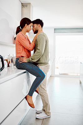 Buy stock photo Cropped shot of an affectionate couple kissing in their kitchen