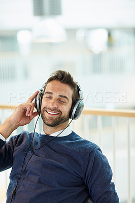 Buy stock photo Shot of a young businessman listening to music in an office