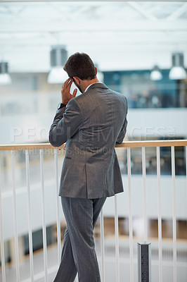 Buy stock photo Rearview shot of a young businessman looking stressed out while standing in an office