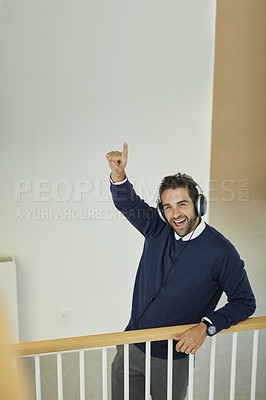 Buy stock photo Portrait of a young businessman wearing headphones and pointing up in an office