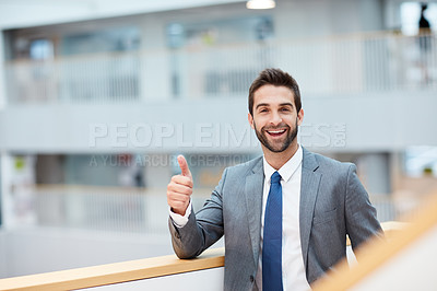 Buy stock photo Portrait of a young businessman showing thumbs up in an office