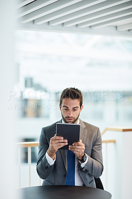 Buy stock photo Shot of a young businessman looking shocked while using a digital tablet in an office