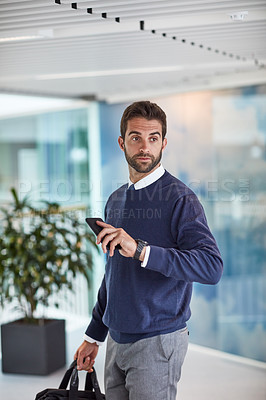 Buy stock photo Shot of a young businessman holding a cellphone and a bag