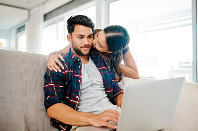 Buy stock photo Shot of an affectionate young woman kissing her boyfriend on the cheek while he's working on his laptop at home