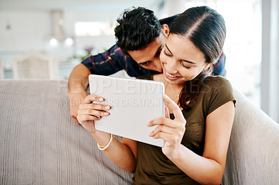 Buy stock photo Shot of an affectionate young man kissing his girlfriend on the cheek while she's using her digital tablet at home