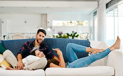Buy stock photo Full length shot of a young couple relaxing together in their living room at home