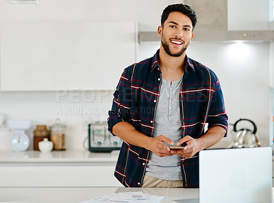 Buy stock photo Shot of a handsome young man using his cellphone and laptop in his kitchen at home