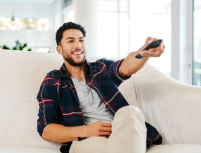 Buy stock photo Shot of a handsome young man switching channels with a remote controller while watching tv at home