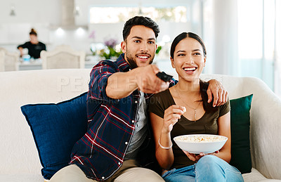 Buy stock photo Shot of an affection young couple watching tv together in their living room at home