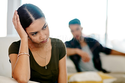 Buy stock photo Shot of a young woman looking upset after having an argument with her boyfriend at home