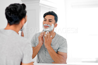 Buy stock photo Shot of a handsome young man applying shaving cream on his beard in the bathroom at home