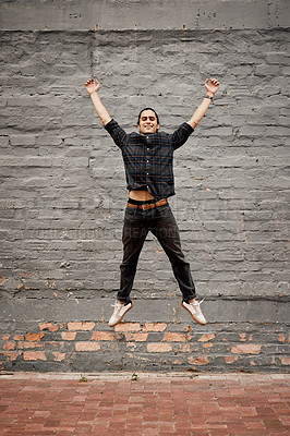 Buy stock photo Full length portrait of a handsome young man jumping up in the air while outside during the day