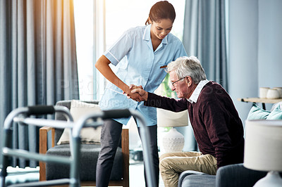 Buy stock photo Shot of a young nurse helping a senior man get up from his chair