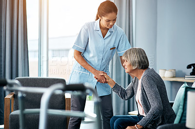 Buy stock photo Shot of a young nurse helping a senior woman get up from her chair