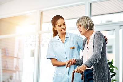 Buy stock photo Shot of a young nurse helping a senior woman with a walking stick
