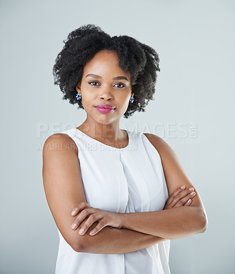 Buy stock photo Cropped portrait of an attractive young woman standing with her arms folded against a gray background in the studio