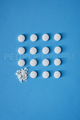 Buy stock photo Studio shot of tablets arranged in the shape of a square with one being crushed against a blue background