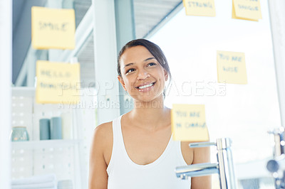 Buy stock photo Cropped shot of an attractive young woman looking at her notes on the bathroom mirror at home