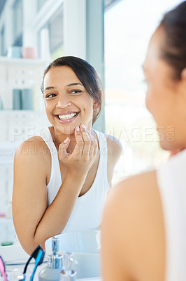 Buy stock photo Cropped shot of a attractive young woman admiring her skin in front of the bathroom mirror at home