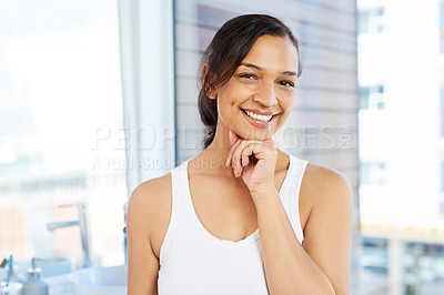 Buy stock photo Cropped portrait of an attractive young woman standing with her hand on her chin in her bathroom at home