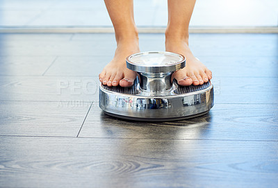 Buy stock photo Cropped shot of an unrecognizable young woman standing on a weight scale at home