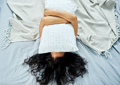 Buy stock photo High angle shot of an attractive young woman holding her eyes closed with a pillow while lying on top of her bed at home