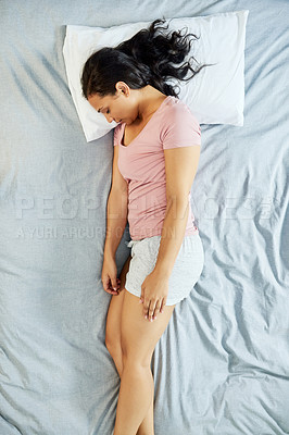 Buy stock photo High angle shot of a tired young woman lying on top of her bed trying to get some rest during the morning hours