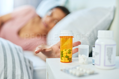 Buy stock photo Shot of a carefree young woman reaching out to grab a container with pills in it while lying on her bed at home
