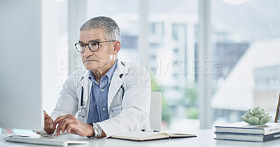 Buy stock photo Cropped shot of a mature male doctor in his office