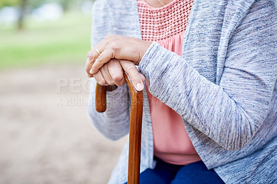 Buy stock photo Cropped shot of an unrecognizable senior woman holding her walking stick while in the park during the day